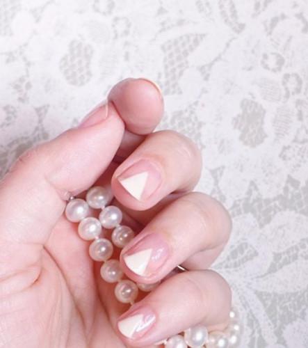 """Bạn yêu những mẫu móng tay kiểu Pháp? Hãy """"nâng cấp"""" cho đôi bàn tay của mình bằng cách biến những đường viền móng tay màu trắng đơn thuần thành những hình tam giác tông trắng trên nền móng màu nude trang nhã. Mẫu thiết kế này sẽ khiến giúp bạn trông tinh tế, nhẹ nhàng hơn rất nhiều."""