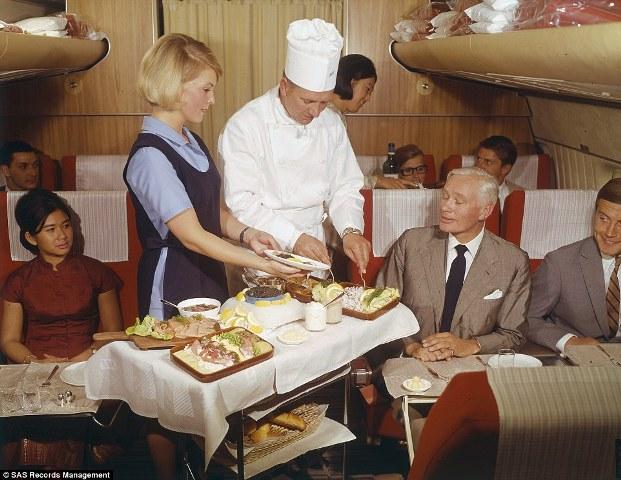 Trong khoang hạng nhất vào năm 1969, nữ tiếp viên đang cho khách xem đĩa thức ăn trong khi đầu bếp cắt một phần hải sản