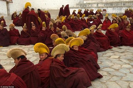Các nhà sư học tập tại học viện Phật giáo Gelugpa của Tây Tạng. Trong ảnh, các nhà sư đang ngồi chờ bên ngoài gian thờ chính của tu viện Labrang.