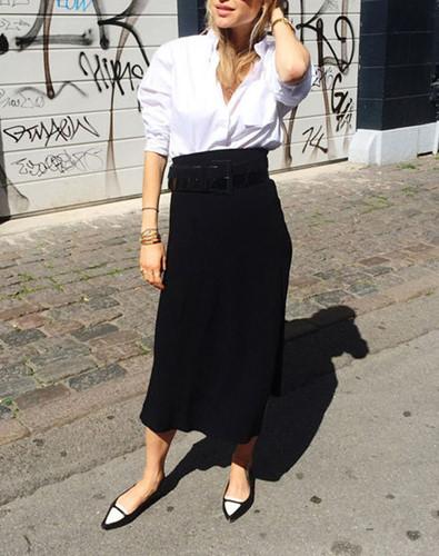 Áo sơ mi được sơ vin kết hợp với chân váy midi tạo nên phong cách doanh nhân lịch sự mà vẫn thoải mái.