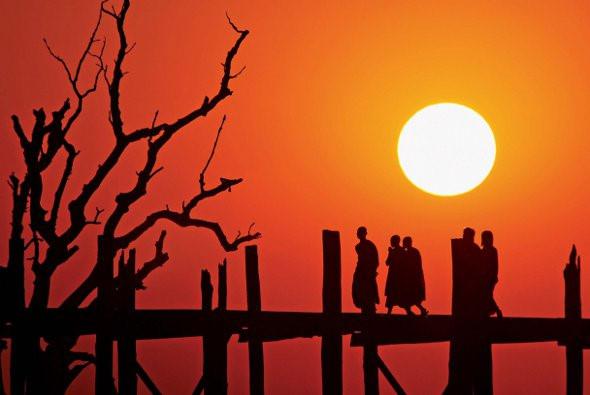 Cây cầu U Bein đẹp nhất vào những buổi chiều tà, những hình ảnh ấn tượng của hoàng hôn màu cam vàng rực rỡ phủ lên cây cầu, xuyên qua những cọc gỗ có lẽ đây sẽ là cảnh tượng đẹp nhất của đất nước Myanmar. Ảnh: photonews.
