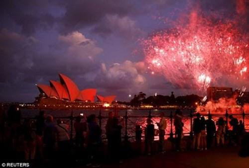 Nhà hát Opera và cầu cảng tại Sydney, Australia chuyển màu đỏ trong khoảnh khắc Giao thừa.