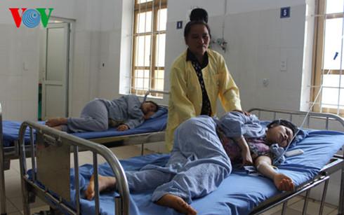 Bà Lò Thị Bên (áo vàng) đang chăm sóc người nhà bị ngộ độc. (Ảnh: VOV)