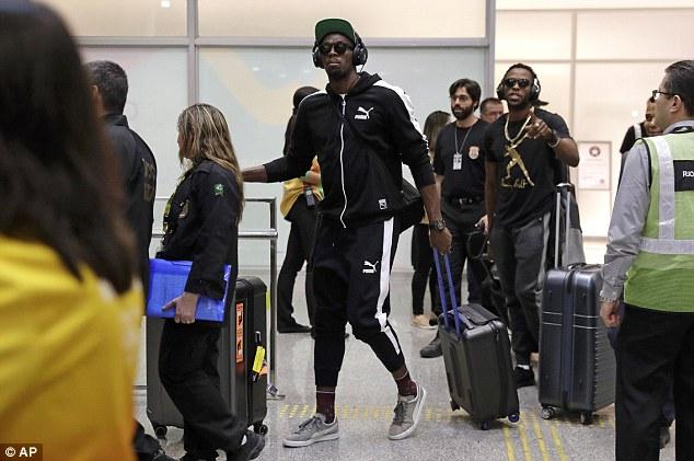 Usain Bolt xuất hiện ở sân bay với tai nghe và kính râm.