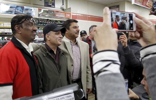 Từ trái sang: nhân viên của cửa hàng 7-Eleven M.Faroqui, quản lý Bally Gosal và ông chủ Balbir Atwal chụp ảnh khi mọi người đổ đến chúc mừng Ảnh: Reuters