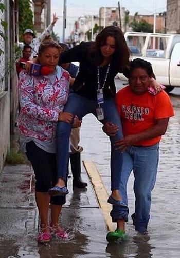 Nữ phóng viên Lydia Cumming được hai người dân bế qua chỗ ngập nước. Ảnh: Twitter