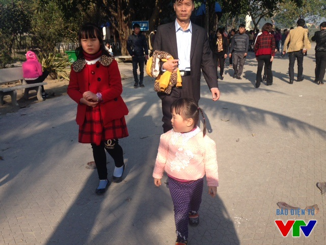Các em bé cũng theo cha mẹ đến đền Ông Hoàng Mười để du xuân trong năm mới