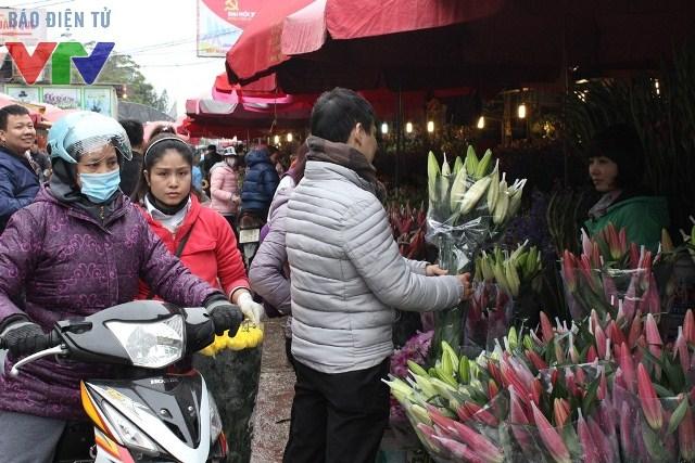 Nhiều người Hà Nội tranh thủ dịp cuối tuần tìm mua hoa đẹp tại chợ Quảng Bá để trang trí nhà cửa dịp giáp Tết