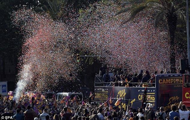 Pháo hoa giấy ngợp trời nơi chiếc xe của các cầu thủ FC Barcelona đi qua.
