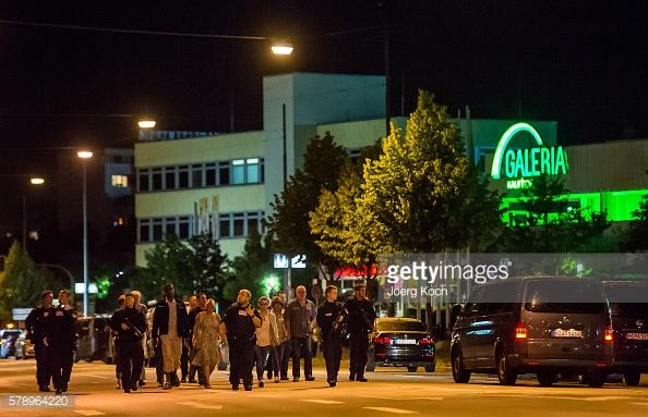 Nhân viên cảnh sát hộ tống người từ bên trong trung tâm mua sắm sau vụ nổ súng tại Olympia Einkaufzentrum.