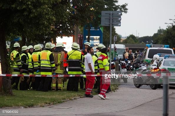Nhân viên cứu hỏa túc trực bên ngoài trung tâm mua sắm Olympia Einkaufzentrum Munich sau vụ xả súng khiến ít nhất 9 người thiệt mạng. Giới chức nghi ngờ vụ việc có khả năng là một cuộc tấn công khủng bố.