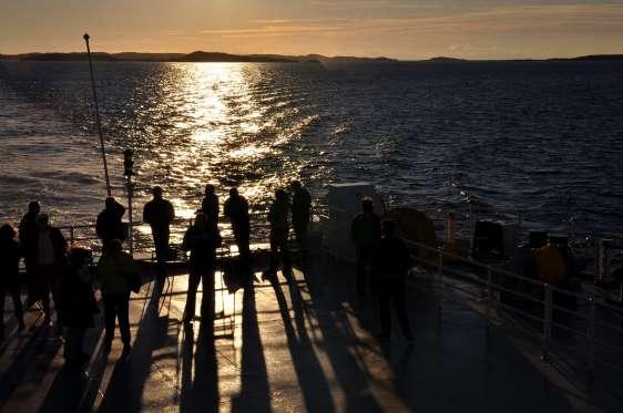 Một nhóm người đang đứng trên phà thưởng thức cảnh Mặt trời mọc lúc nửa đêm.