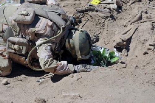 Một binh sĩ Iraq quỳ trước mộ tập thể ở Tikrit. (Ảnh: Reuters)