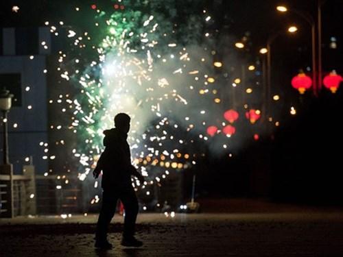 Một người đàn ông Trung Quốc đốt pháo hoa mừng năm mới bên bờ sông Áp Lục, ngăn cách lãnh thổ Trung Quốc và Triều Tiên.
