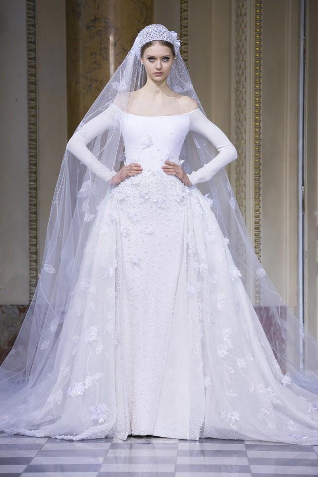 Cô dâu của Georges Hobeika diện váy cưới trễ vai, tạo điểm nhấn ở eo. Khăn voan dài được thiết kế khá ấn tượng.