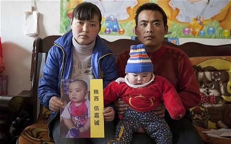 Anh Wu Xinghu cùng vợ với ảnh em bé bị bắt cóc (Ảnh: Telegrahp)