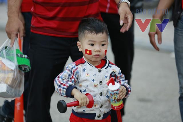 """Trẻ em theo gia đình đến cổ vũ cho đội tuyển cũng được người lớn """"trang điểm"""" cho những tấm decal hình quốc kỳ Việt Nam ngộ nghĩnh trên má."""