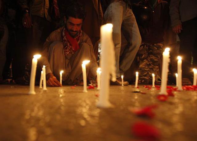 Một người đàn ông đốt nến tưởng niệm các nạn nhân. (Ảnh: Reuters)