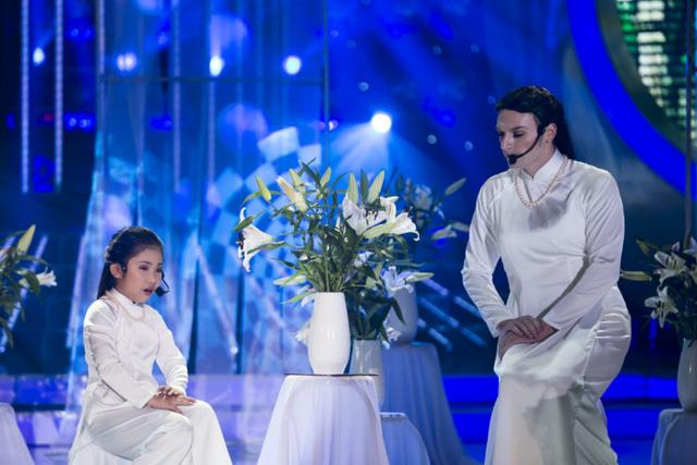 Bé Uyên Nhi và ca sĩ Kyo York cùng diện áo dài trắng thướt tha, sắm vai diva Mỹ Linh, thể hiện ca khúc Chị tôi rất cảm xúc