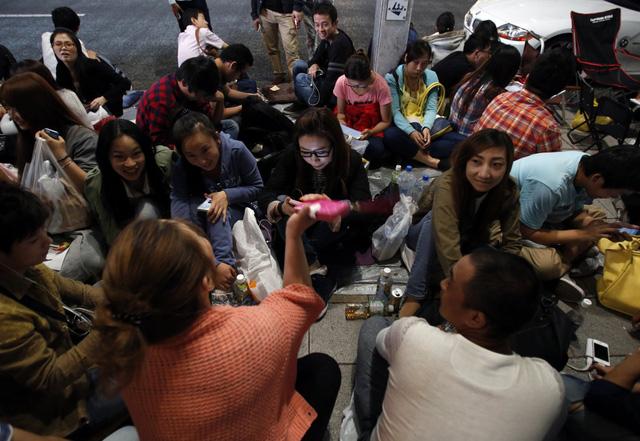 Các tín đồ của iPhone 6 ngồi chờ trước cửa hàng tại Tokyo, Nhật Bản
