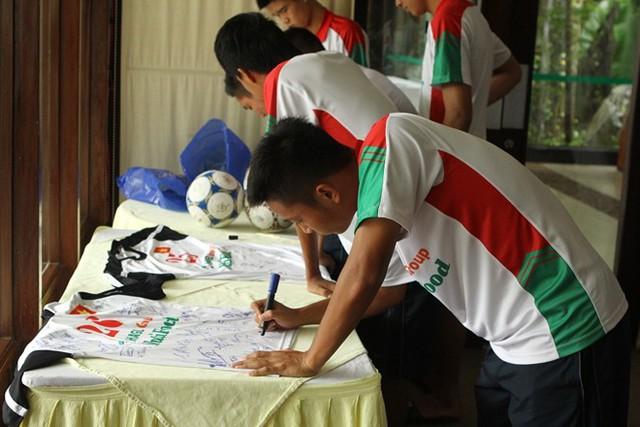 Trong lúc chờ đợi bầu Đức, các cầu thủ U19 Việt Nam tranh thủ ký áo đấu...