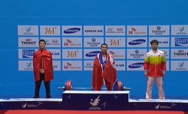 Dù phá kỷ lục ASIAD nhưng Thạch Kim Tuấn (trái) vẫn không thể giành được HCV chung cuộc ở môn cử tạ nam hạng 56kg.