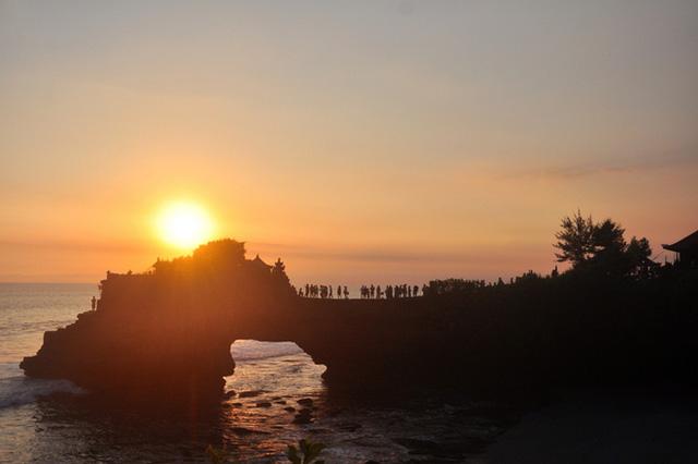 Khoảnh khắc bình yên khi ánh hoàng hôn lan tràn ngôi đền thiêng. Tanah Lot nổi tiếng vì được xây dựng trên đỉnh của một hòn đá khổng lồ giữa biển. Bên cạnh đó, nơi đây còn là một trong những ngôi đền chính trong chuỗi thờ phụng các vị thần Bali.
