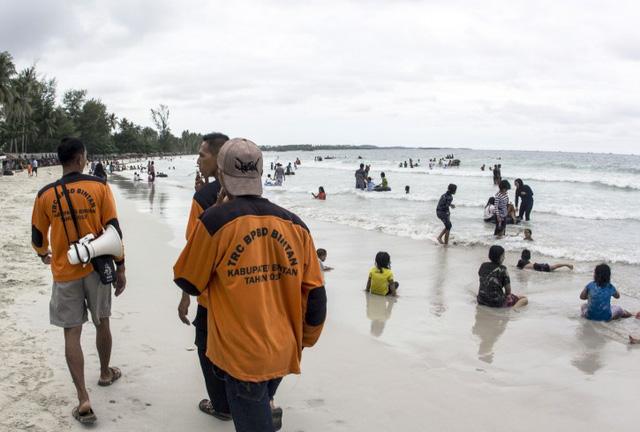 Thành viên của Cơ quan quản lý thiên tai Indonesia đi bộ tại một bãi biển tại đảo Bintan, Indonesia, khi tìm kiếm những người mất tích máy bay AirAsia.
