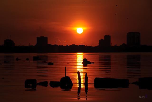Mặt trời đỏ quạnh như trái cầu lửa dần khuất xuống mặt hồ yên ả.