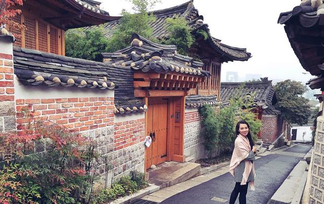 MC Minh Hà tại làng cổ Bukchon Hanok - nơi được chọn làm bối cảnh cho nhiều bộ phim cổ trang Hàn Quốc. Nữ MC chia sẻ: Các ngôi nhà ở khu vực này tuy có tuổi đời hàng trăm năm nhưng được bảo tồn tốt. Hiện tại, người dân vẫn sinh sống tại đây. Nơi đây được xem là khu nhà giàu, bởi những gia đình sinh sống tại đây trước kia đều thuộc dòng dõi hoàng tộc. Khu làng này cũng nằm gần cung điện xưa.