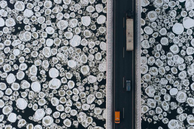 Những chiếc xe tải và xe ô tô đang di chuyển trên một con đường băng qua sông Vistula gần làng Kiezmark, Ba Lan. (Ảnh: Kacper Kowalski—Panos Pictures)