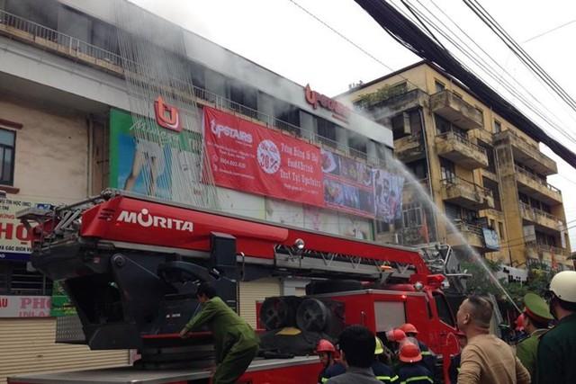 Lực lượng PCCCphun nước vào tầng 3 tòa nhà có đám cháy.(Ảnh: Sơn Bách/Vietnam+)