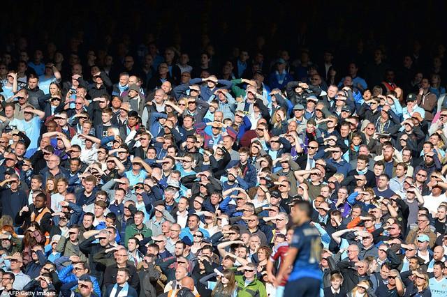 Hình ảnh ấn tượng: Hàng loạt CĐV trên sân Upton Park giơ tay che mắt vì nắng theo dõi trận đấu.