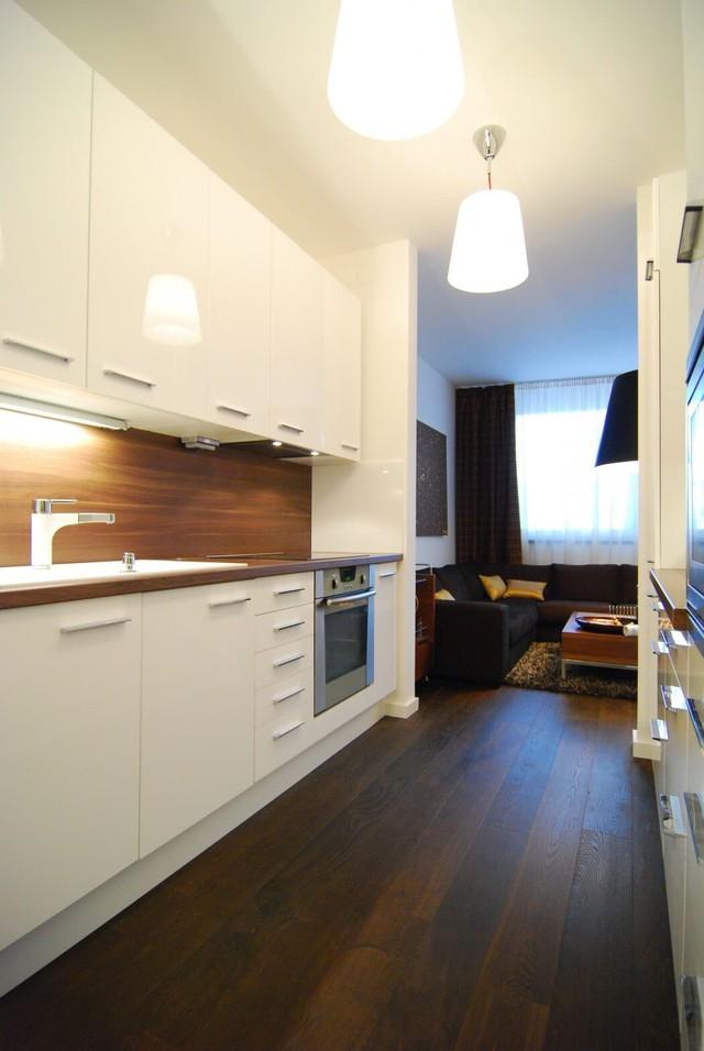 Trái với gam màu trầm của phòng khách, căn bếp dường như bừng sáng với màu trắng tinh khôi. Sử dụng màu trắng trong phòng bếp cũng tạo nên cảm giác sạch sẽ, gọn gàng