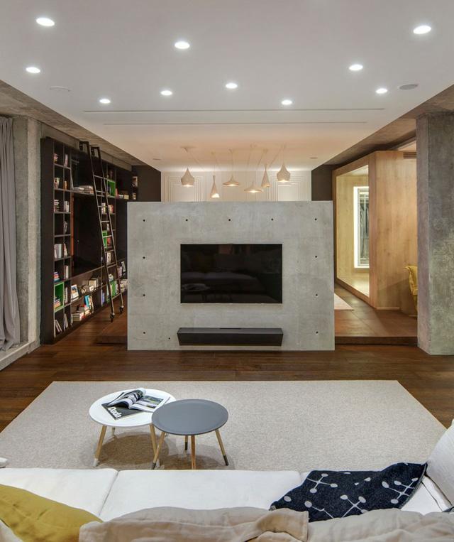 Cảm nhận đầu tiên khi bước vào căn hộ này là sự thiếu vắng của những bức tường. Vì muốn hướng tới một không gian mở, chủ nhân căn hộ đã loại bỏ hầu hết tất cả các bức tường. Trong ảnh, đằng sau tấm vách treo TV chính là phòng ngủ