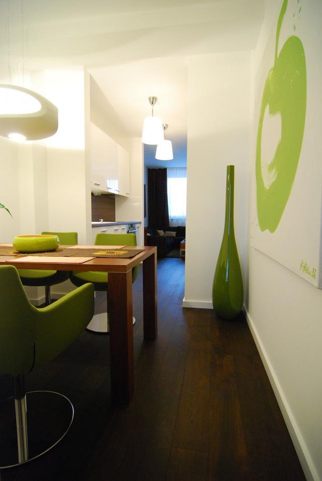 Phòng ăn liên thông với bếp và được tô điểm bằng màu xanh cốm dịu mát