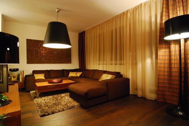 Trung tâm của phòng khách là chiếc sofa lớn - nơi gia đình quây quần sum họp sau những giờ làm việc, học tập mệt nhọc. Mảng tường đằng sau chiếc sofa được trang trí bằng một tấm tranh khổ lớn, khiến không gian trở nên rộng rãi hơn