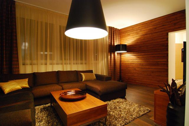 Căn hộ gây ấn tượng với tông màu nâu trầm của gỗ. Việc ốp gỗ cả mảng tường cũng mang đến một cảm giác sang trọng, ấm áp