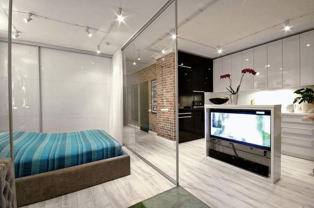 Chủ nhân căn hộ đã sử dụng đảo bếp không chỉ để treo TV mà còn như một vách ngăn chia cách không gian phòng bếp và không gian chung. Nằm trong phòng ngủ, bạn cũng có thể xem được TV một cách dễ dàng