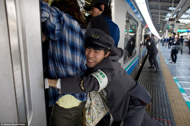 Một trạm tàu điện ngầm ở Tokyo hoạt động hết công xuất nhưng dường như vẫn không đủ đáp ứng số lượng người quá tải. Các hàng khách phải chen lấn, bám vào nhau để vào khoang.