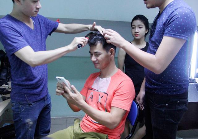 MC Xuân Bắc tranh thủ kiểm tra điện thoại trong khi được các chuyên gia trang điểm giúp tạo kiểu cho mái tóc.