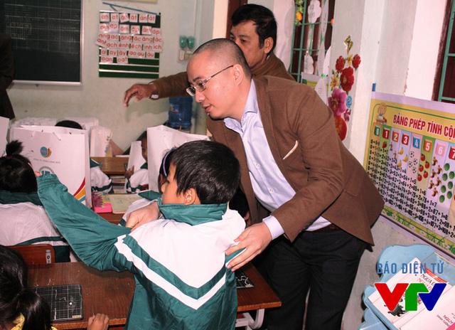 Ông Nguyễn Phan Huy Khôi, đại diện Công ty Tân Hiệp Phát mặc áo ấm cho các em học sinh trường Ba Rền