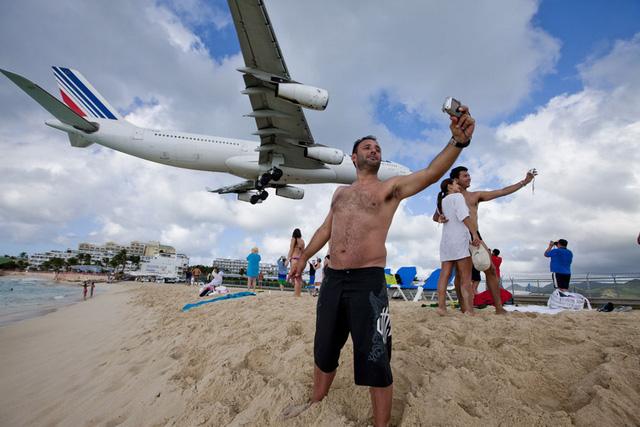 Du khách selfie khi máy bay chuẩn bị hạ cánh.Máy bay đang hạ cánh xuống sân bay quốc tế Princess Juliana ở Saint Maarten. Nó bay ngang qua một bãi biển du lịch nổi tiếng, lướt ngay sát trên đầu khách du lịch.