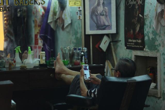 Người thợ cắt tóc trong phố cổ tranh thủ lên mạng cập nhật tin tức với 3G.