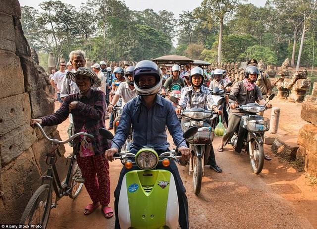Các phương tiện như xe đạp, xe máy nối đuôi nhau trên những con đường quanh khu vực đền Angkor Wat, Siem Reap, Campuchia.