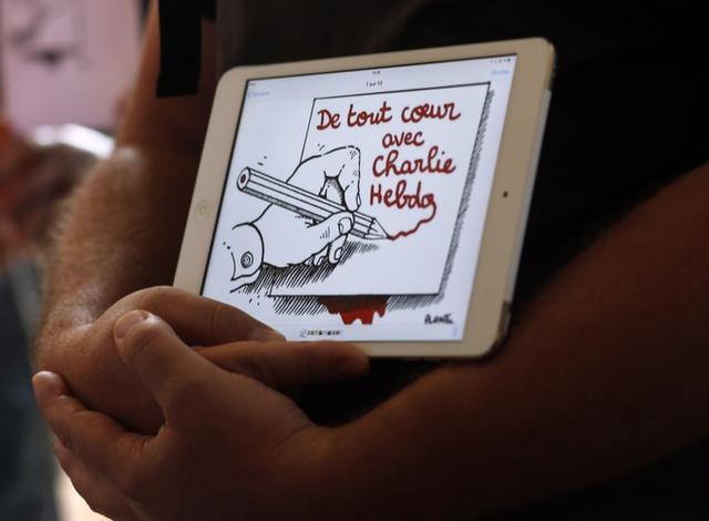 Dòng chữ Một lòng hướng về Charlie Hebdo được hiển thị trên máy tính bảng của một trong những người tham dự lễ tưởng niệm ở Đại sứ quán Pháp tại Buenos Aires, Argentina.