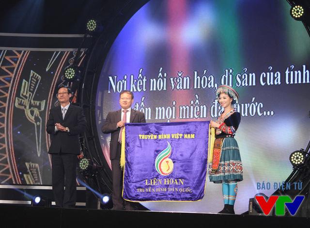Ông Phan Quang Hưng, Giám đốc Đài PT-TH Lào Cai và ca sĩ Bảo Yến - một người con của Lào Cai - cùng nhận cờ đăng cai tổ chức LHTHTQ lần thứ 36 từ ông Lê Khánh Hòa - Giám đốc Đài PT-TH Quảng Bình