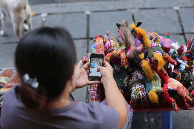 Những người bán đồ lưu niệm đang tranh thủ vào mạng xem tin tức lúc bán hàng. Tại đây, sóng 3G Viettel rất mạnh và phủ lượng trạm dày đặc, giúp người dùng vào mạng, lướt Facebook dễ dàng.