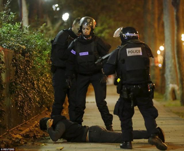 Một thanh niên nằm xuống đất khi cảnh sát kiểm tra danh tính gần phòng hòa nhạc Bataclan