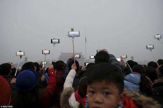 Người dân Bắc Kinh phải sử dụng gậy selfie và smartphone để quan sát từ xa do tầm nhìn bị che bởi khói bụi